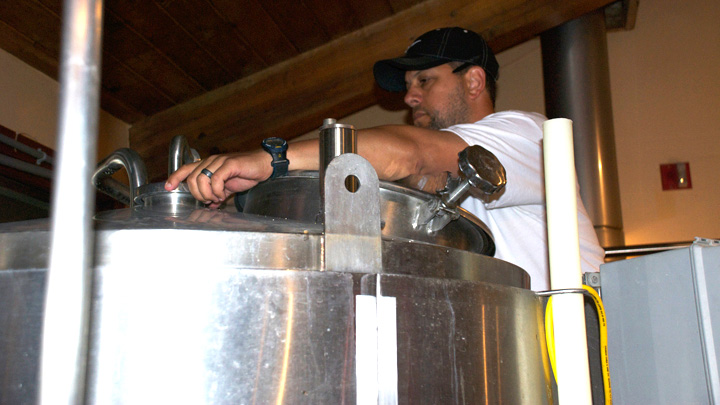 Photo of Craft Beer Brewer checking tank guages.